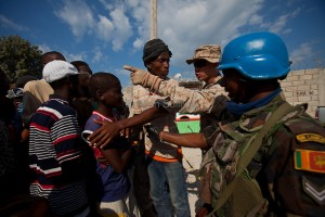 A Haitain man, U.S. Marine and Sri Lankan U.N. soldier help organize a line for food tickets west of Port-au-Prince.